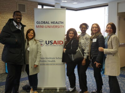 A group of participants pose with the Mini-University sign